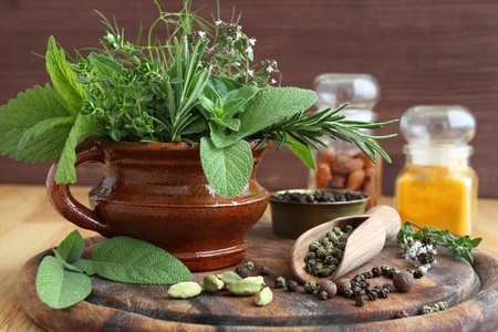 Bunch of fresh aromatic herbs in a ceramic pot and spices. photo