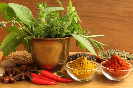 Spices and bunch of fresh aromatic herbs in brass pot. photo