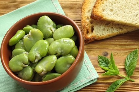 broad: Bowl of green boiled broad beans and bread Stock Photo