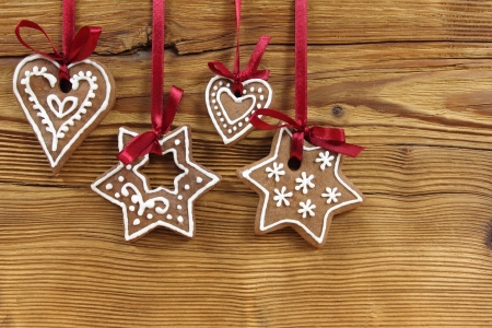 Gingerbread cookies hanging on wooden background. Christmas decoration. Stock Photo