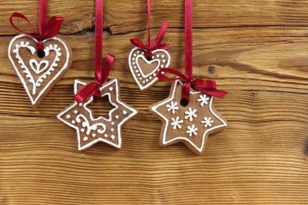 Koekjes van de peperkoek opknoping op houten achtergrond. Kerst decoratie.