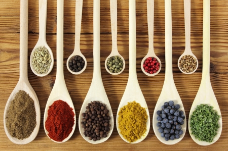 juniper: Colorful spices in wooden spoons - beautiful kitchen image.