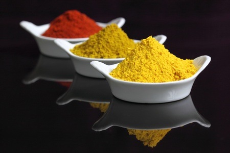 curry powder: Spices in small white bowls. Includes curry powder, turmeric and pepper powder.