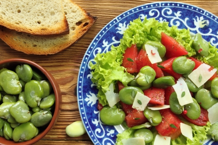 queso de cabra: Primer plano de una ensalada de habas con queso de cabra y tomate