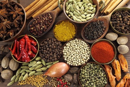 food additives: Spices and herbs in metal  bowls and wooden spoons. Food and cuisine ingredients. Stock Photo