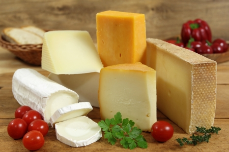 Cheese board - various types of soft and hard cheese. International dairy delicacies.