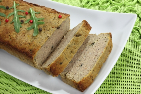 fayre: Fresh meat pate on  a white plate. Green background. Stock Photo