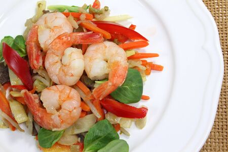 Fried shrimp on a salad of steamed vegetables photo