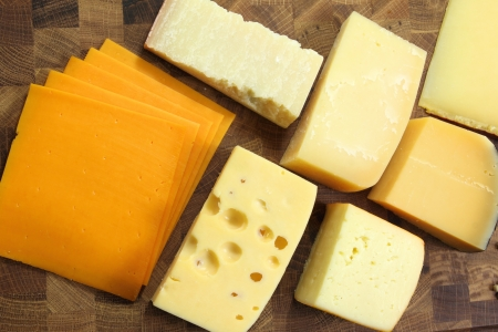 parmezan: Different types of hard  cheeses on a wooden board. Stock Photo
