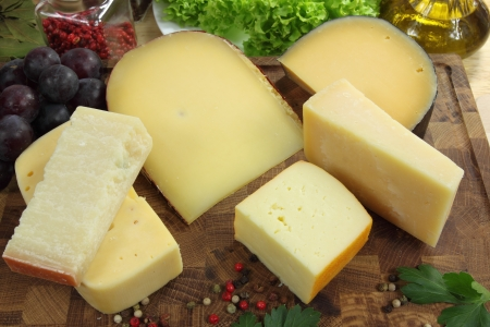 parmezan: Different types of hard and mold cheeses on a wooden board.