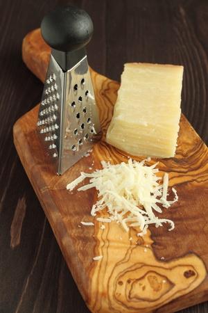 queso rallado: Queso rallado sobre tabla de madera con una madera de olivo.