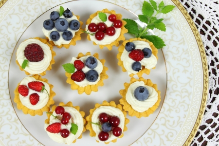 Fresh delicious fruit tarts with cream and berries on a plate photo
