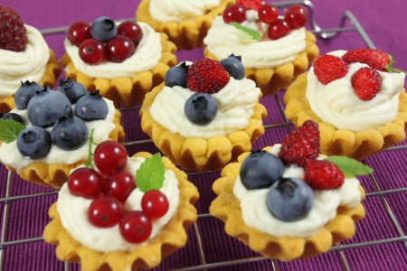 Fresh delicious fruit tarts with cream and berries  photo