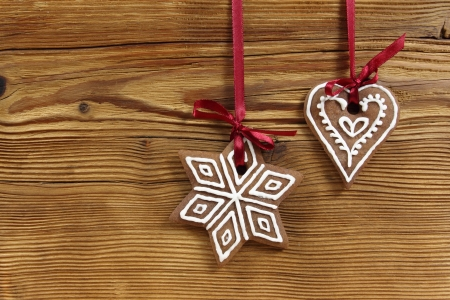 Gingerbread cookies hanging on wooden background. Christmas decoration. photo