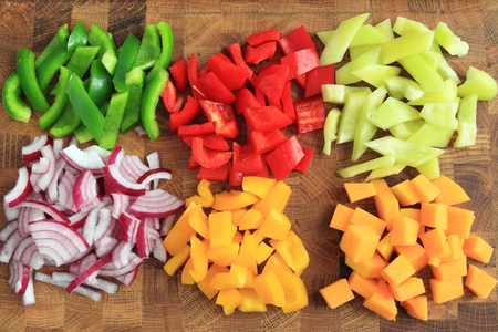 Colored peppers and onions diced on a chopping board photo