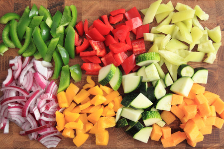 Colored peppers and onions diced on a chopping board Standard-Bild