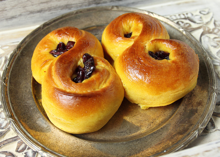 Sweet Swedish buns baked with saffron, cranberries and raisins Stock Photo - 25667952
