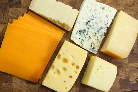Different types of hard and mold cheeses on a wooden board. photo
