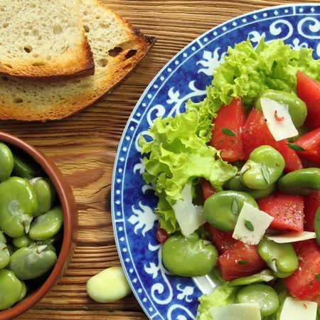 square composition: Close up of a broad beans salad with tomato and goat cheese. Square composition. Stock Photo