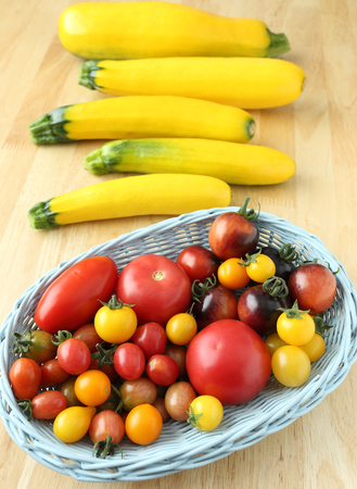 cherry varieties: Different varieties of tomatoes in a basket and zucchini.