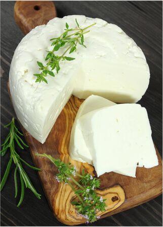 queso blanco: Queso blanco cortado en una tabla de madera