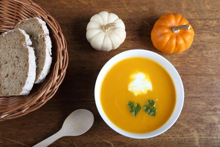 Pumpkin soup in white bowl on wooden background. photo
