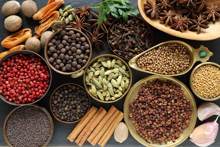 fenugreek: Spices and herbs on black ceramic  background. Food and cuisine ingredients.