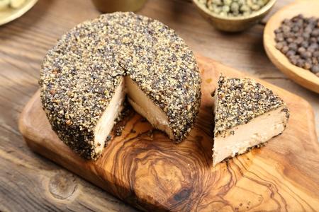 queso de cabra: Queso de cabra madurado con granos de pimienta negro. Foto de archivo