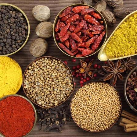 badian: Colorful, aromatic Indian spices on a wooden background. Stock Photo
