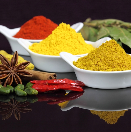 additives: Spices and herbs in white ceramic bowls. Food and cuisine ingredients. Colorful natural additives. Stock Photo