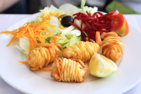 Salad and fried shrimp wrapped in potato strips.