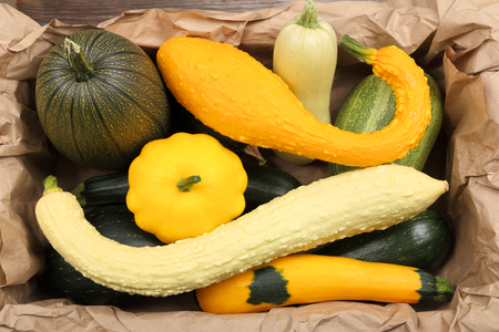 courgettes: Courgettes and squashes stacked in a box on a paper. Stock Photo