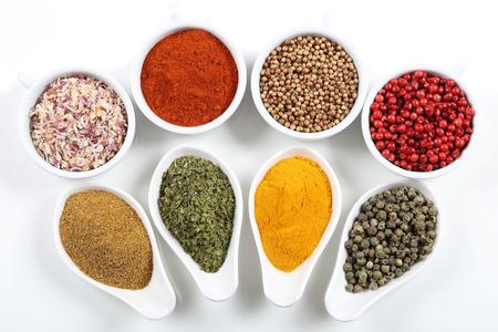 especias: especias de colores, llenos de sabor en tazones de cerámica en el fondo blanco.