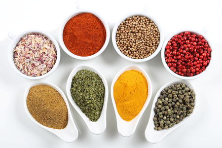 sapid: Flavorful, colorful spices in ceramic  bowls on white background.