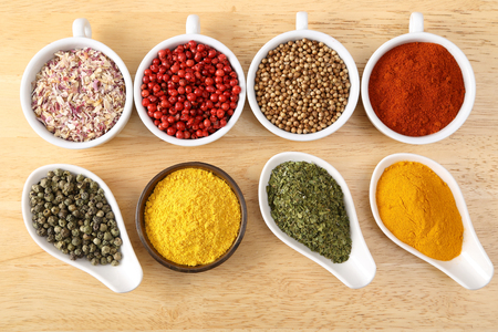 sapid: Flavorful, colorful spices in ceramic bowls on wooden background.