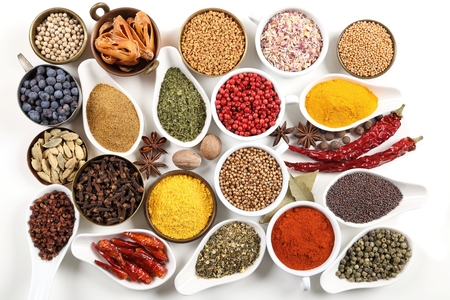 sapid: Flavorful, colorful spices in ceramic and metal bowls on white background. Stock Photo