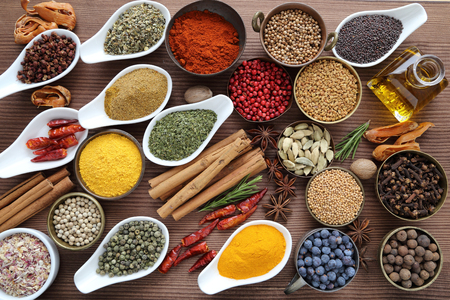 indian food: Flavorful, colorful spices in ceramic and metal bowls on wooden background.