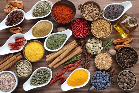 cibo: Saporito, spezie colorate in ciotole di ceramica e metallo su fondo in legno.