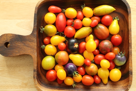 variety: Colorful different kind tomatoes in wooden bowl. Stock Photo