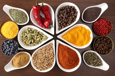 flavorful: Flavorful, colorful spices in metal and ceramic bowls on dark wooden background.