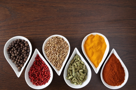 flavorful: Flavorful, colorful spices in ceramic bowls on dark wooden background. Stock Photo