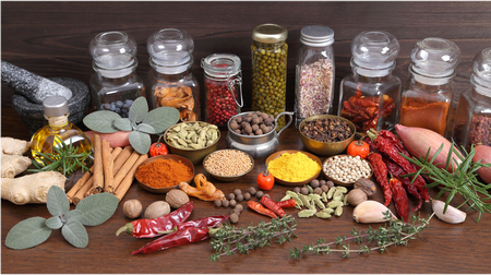 odorous: Flavorful, colorful spices in metal  bowls and glass bottles on dark wooden background.