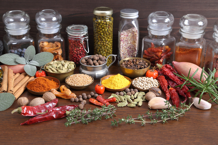 flavorful: Flavorful, colorful spices in metal  bowls and glass bottles on dark wooden background.