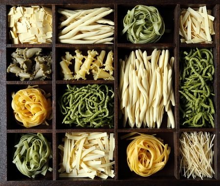 kinds: Different kinds of pasta in a wooden box. Stock Photo