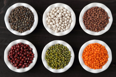 assortment: Colorful beans and lentils in ceramic bowls on a dark background.