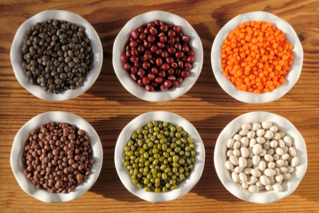 adzuki bean: Colorful beans and lentils in ceramic bowls on a wooden background. Stock Photo