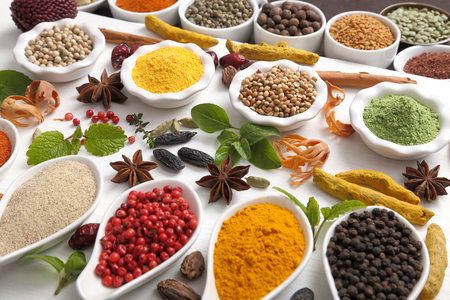 Colorful, aromatic Indian spices and herbs on a wooden white  background.