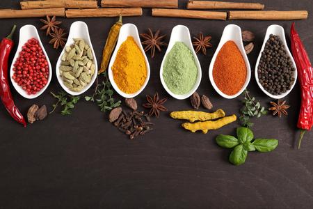 especias: Colorido, especias indias aromáticas y hierbas en un fondo de madera.