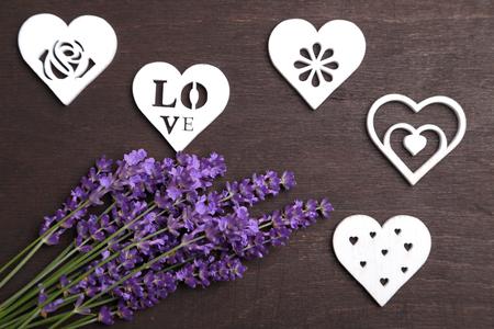 fondos violeta: Un ramo de lavanda y el corazón de madera sobre un fondo oscuro. Foto de archivo