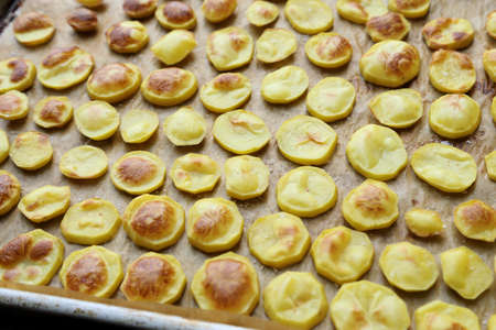 roast potatoes: Slices of roast potatoes on a baking tray and paper. Stock Photo